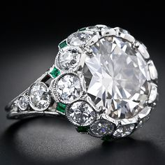 This glorious and impressive diamond ring sizzles with a 5.92 carat transitional European/brilliant-cut diamond.  The magnificent platinum, diamond mounting, created to emulate classic and sophisticated Art Deco style, also sparkles mightily with 2.75 carats of bright-white, European-cut diamonds set in milgrained bezels, punctuated with tiny, square-cut, diagonally-set accent emeralds.  Lang Antiques.