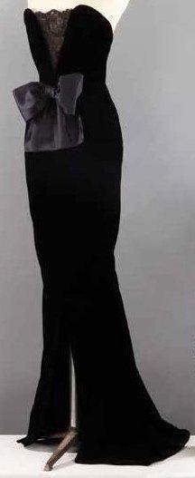 Yves SAINT-LAURENT Haute couture n° 55328 circa 1980 Robe longue en velours de soie noir au bustier agrémenté d'un effet de modestie en dentelle souligné d'un noeud de satin, devant fendu à ourlet arrondi… - Gros & Delettrez - 14/10/2013