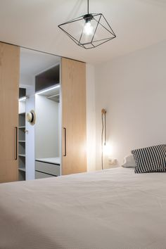 dormitorio con vestidor anexo en melamina textil e iluminación integrada acompañado por puertas de maple