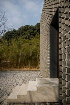 Overlapping bricks give a perforated facade to this mountainside building.