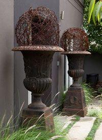 Wire balls set in pedistal urns at entrance