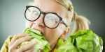 Blonde woman with the scary expression on her face while eating cabbage leaf.