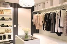 clean, modern closet/dressing room w/glass top island, custom shoe wall, striped black on black wallpaper & great light fixture!