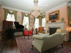 Love the peach walls with the green window treatments and the pop of red in that chair