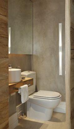 """cuba redonda (Interbagno) apoiada na bancada de madeira de demolição (35 cm de profundidade). """"Já o espelho toma toda a largura da parede para ampliar o espaço"""", explica Andréa. Uma arandela embutida na parede lateral e LEDs atrás do espelho garantem a luz indireta. Nas paredes, a textura imita o cimento queimado (Bricolagem Luzes e Cores)."""