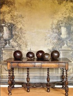 Love the masculine/feminine juxtaposition with the gorgeous antique console table and wood balls set in front of the romantic mural.
