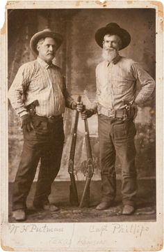 A standing studio portrait of Texas Rangers W. H. Putnam and Captain Phillips both proudly displaying Colt Single-Action Army revolvers and Winchester rifles. Specifically, Putnam holds a lever action Winchester Model 94 rifle and Phillips a Winchester Model 1873.