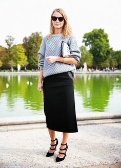 A cable knit gray sweater is worn with a black midi skirt, strappy pumps, a clutch bag, and black sunglasses