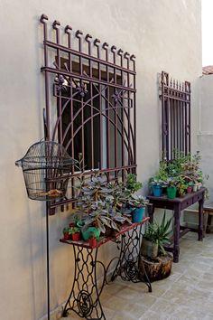 Patio de una casa con una jaula y una mesa que se armó con la estructura de una máquina de coser para sostener plantas.