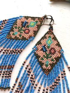 Beaded fringe earrings inspired by Native American styles of beading, in sky blue, clay, and dark balsam green, with a touch of copper and dark blue. These statement earrings have a floral design in the center of the diamond. These lightweight shoulder dusters gracefully brush the collar bone. DIMENSIONS: 5 long x 1.5 wide  READY TO SHIP  --------------->>>>><<<<<--------------->>>>><<<<<--------------->>>>><<&l...