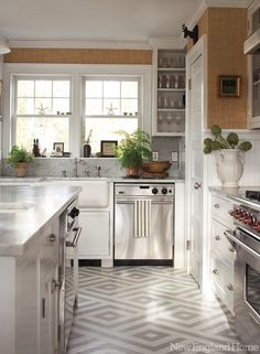 Kitchen by Designer Mary McDonald. Carrara marble bench tops, hand-painted ivory cabinetry with charcoal island, polished nickel pendants, floor of engineered stone in chevron pattern, touches of soft aqua and blue.