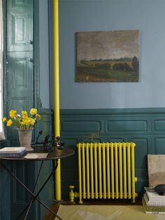 Paint scheme.  Bright radiator, pipe, and flowers contrast cool color scheme tamed by the dark artwork. Bright colors bring life and energy into the room