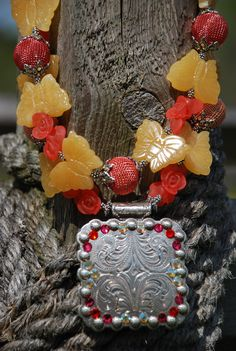 "This gorgeous one-of-a-kind, chunky, double strand Rodeo Cowgirl Necklace is made Carved Yellow Jade Butterflies, Metal Mesh Beads, Yellow Faceted Beads, Coral Acrylic Flowers & adorned with Tibetan Silver bead spacers & bead caps. Topped off with a 2-1/4 x 2-1/4"" Square Concho Pendant embellished with Swarovski Crystals for added Bling. Finished with a nice magnetic clasp. The shorter strand is 19-1/4 and the longer strand is 21. Comes with Organza Jewelry Pouch for storage. This is an…"
