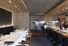 The use of slatted timber structures within this restaurant work extremely well to create subtly defined seating areas. Their open nature allows the raw concrete building to seep through into the design and is also used to conceal the lighting.