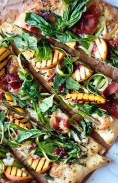 Summer salad pizza with creamy brie cheese, prosciutto, grilled peaches and salad greens