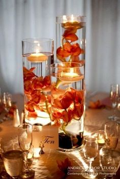 Vases with water and float bright red or orange flowers and tea candles