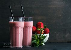Pic: Strawberry and mint smoothie in tall glasses bawl of fresh berries on dark rustic wood background
