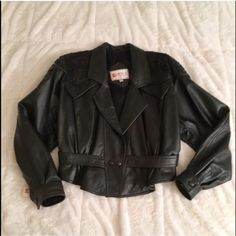 Vintage 80's Cropped Leather Jacket from Turkey Vintage cropped black leather jacket bought in Turkey. Has shoulder pads (as you'd see in 80's fashion) and embroidery along the top of the coat, as seen in the pictures. Measures approx 20 inches across the shoulders, 21 inches down the arm, and 22-24 inches (higher in back, lower in front) from top hemline to bottom hemline. Still has the original tag and was never worn out, but has some signs of age from storage, as seen in the third…