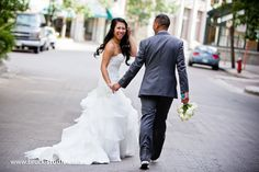 Filipino wedding photography in Winnipeg by vancouver wedding photographer Trevor Brucki.  Walking down street downtown Winnipeg, Exchange district.  Laughing bride holding hands.
