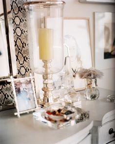 Details Photo - A hurricane lamp and a collection of glass, crystal, and Lucite on a white chest of drawers