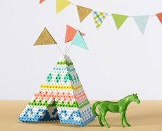 Make this colorful teepee from Perler beads, complete with coordinating flags. The pretty patterns make it fun to do!
