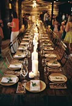 Table setting: candles in middle, white napkins folded on plate with loose greenery