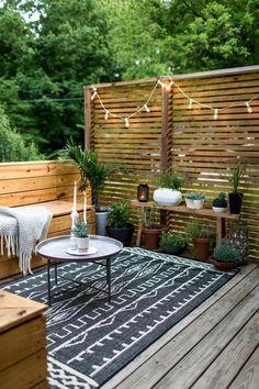 Terrassengestaltung kleiner Teppich grau Sitzecke orientalische Elemente Sichtschutz Lichterkette Kerzen