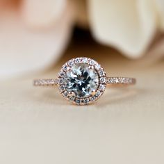 Aquamarine engagement ring set in rose gold with conflict free diamonds. Halo style, round cut.