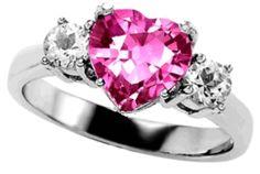 Hermoso anillo con diamante de corazón central color rosa y dos diamante blancos laterales.
