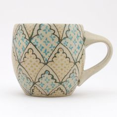 Cup with dark green fluted arch pattern with turquoise and yellow crosses
