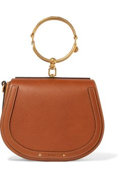 No true #ChloéGIRL's wardrobe is complete without at least one 'Nile' bag in it. Made in Italy from caramel leather, this cult style's recognizable saddle shape is framed by tonal suede panels and a jewelry-inspired gold bracelet handle. Its interior will comfortably fit a small wallet, phone and compact.