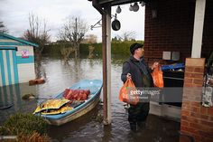 Laleham Reach resident Steve Rastall returns home with supplies of shopping and logs for the fire on February 17, 2014 in Chertsey, United Kingdom. The Environment Agency continues to issue severe flood warnings for a number of areas on the River Thames in the commuter belt west of London.