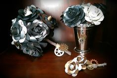 Steampunk-inspired paper flower suite made with black, copper, silver, gray, floral, and musical note paper.  The bouquet is wrapped in twine and adorned with gears for charms.  The boutonniere is wrapped in a silver-y metallic lace also adorned with gears.  And the centerpiece encompasses a silver mint julep cup with touches of gears within the paper flowers and on the outside of the cup  Contact us today to design your custom paper flower arrangements!  Kelly@Angelic-Affairs.com
