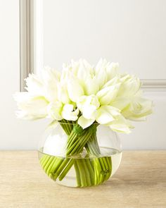 Bundles of white tulips in a round glass vase. Spotted at @neimanmarcus.