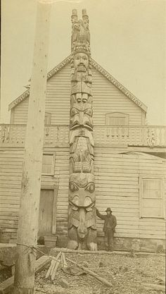 Haida man standing in front of a Haida home with totem, wood shavings in foreground, in the village of Gáwk'yaan (also known as Howkan village), by Edward DeGroff, circa 1880s.