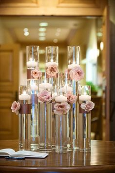 beautiful simple centerpiece design using 2 sizes of cylinder vases - mauve ribbon tied around middle portion of each vase with a garden rose attached to ribbon and floating candle inside vases