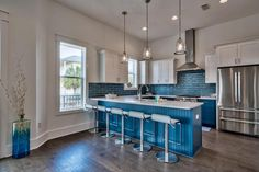 Blue subway tile, quartz counters, stainless steel, blue cabinets