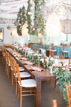Sage green dresses, white and coral peonies, red roses, long table length florals, hanging flower arrangements, copper charges, succulents galore, turquoise filled vases.