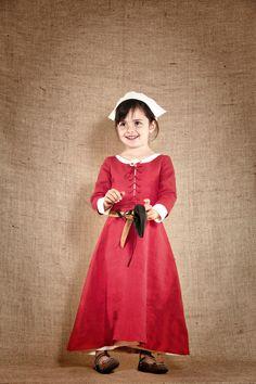 """Costume médiéval de Belle Marianne, châtelaine du 13ème siècle composé de 3 pièces : une sous-robe en lin de couleur blanc cassé, une coiffe réglable assortie, une robe de dessus en lin lourd et lavé de couleur rouge avec laçage sur le devant. Ce costume de fabrication artisanale est disponible du 4 au 12ans à partir de 154€. Carquois, arc et flèches, ceinture et bourse peuvent compléter ce costume. Ces accessoires en cuir et en bois sont également disponibles sur le site de """"7 et une…"""