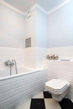 Białe płytki subway tworzące strukturę stylowej cegiełki położono tylko do pewnej wysokości łazienki. Resztę ściany i sufit pomalowano pastelowym odcieniem szarości, zostawiając wąski biały pas dla ozdoby. Stylowa miska sedesowa współgra z retro baterią przy wannie.