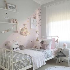 pastel girl's sleeping nook with toys and various wall decor