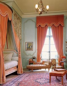 grand bedroom with high ceilings in soft blue and coral-orange bedroom. The draperies help balance the proportion of this room