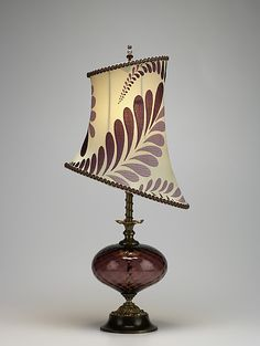 """""""Makaela""""  Mixed-Media Table Lamp    Created by Caryn Kinzig and Susan Kinzig  A lavender blown glass globe adorns the brass stem of this table lamp. The asymmetric silk shade features a leaf design. Beaded finial. 60-watt maximum bulb (40-watt bulb included).     Dimensions: 28.0in H x 13.0in W x 7.5in D"""