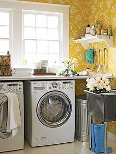 Ruimte voor de wasmachine met fris geel behang.