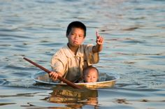 子供たち 孩子們 The kids   Young Cambodian boy floating inside a washbasin on Tonle Sap River, Siem Reap, Cambodia