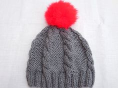 Gray hand knitted cabled hat with fur red pom pom
