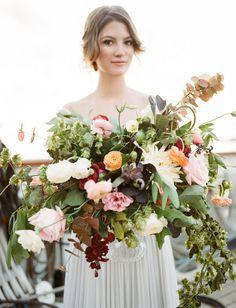 Whimsical floral arrangement with ranunculus, roses, hops vine + more