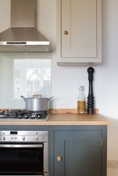 Sustainable Kitchens - The Cosy Stone Cottage Kitchen in Bath. The Neff oven and hood add an industrial feel to an otherwise country shaker style kitchen. The oak worktop and cabinets painted in Farrow & Ball Down Pipe and Shaded White work well together to create a warm feeling.