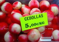 Son las cebollas. ¡Nunca he visto las cebollas en agua o las cebollas con mucho color! Esta imagen representa los colores vibrantes en el mercado.