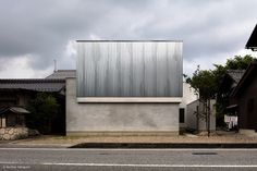 House for a Photographer is a minimalist architecture project located in Shiga, Japan, designed by FORM/Kouichi Kimura Architects. The site is located along an arterial road that runs through countryside. In the neighborhood stand private residences and a grove of the village shrine surrounding a passage to the shrine. The building is made of mortar and galvanized steel sheet which reflects dull light, making it look massive. It is laid out to be accommodated within the L-shaped lot, and…